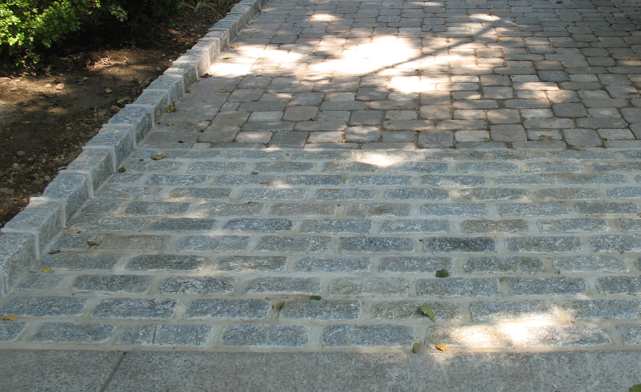 paving stone driveway with cobblestone apron and belgium block curbing