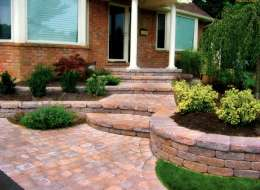 Paving stone entry walkway with evergreen shrubs and flowering perennial plants