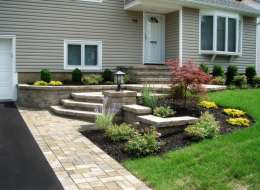 Front entry design with paving stone walkway plant beds and light pier
