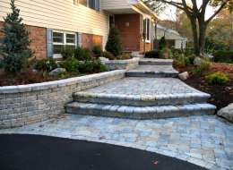 Front entry paving stone walkway design with raised plant bed