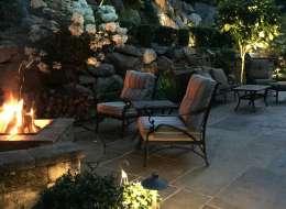 Bluestone flagging patio with bluestone fire pit and stone retaining wall