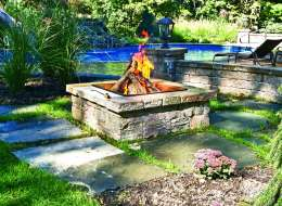 Stack stone fire pit with seat wall and light piers