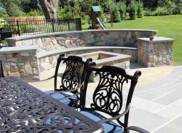 Natural field stone fire pit design with stone bench