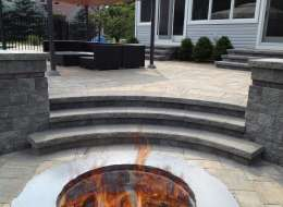 Cambridge paving stone fire pit design with seat wall and piers
