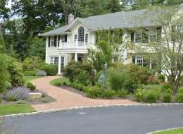 Brick front entry walkway with ornamental shrubs and perennial plants