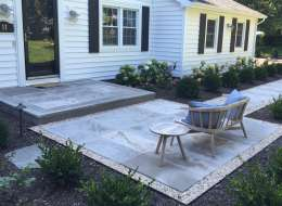 Traditional front walkway design using limestone and evergreen shrubs