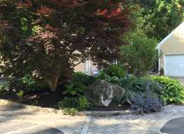 Driveway planting island with ornamental shrubs and flowering perennials