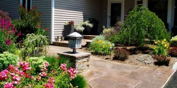 Natural stone front entry with light pier flowering roses and perennial flowers