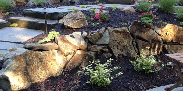 Moss rock retaining wall with bluestone stepping stones