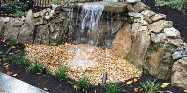 Moss rock pondless waterfall with perennial plants